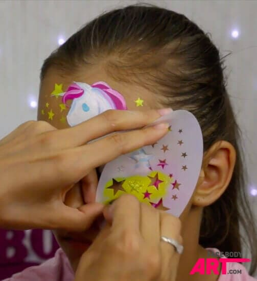 Stenciled shiny element in face painting